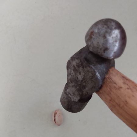 Image of large hammer cracking small nut illustrating the Fairisle article Don't outsource your change